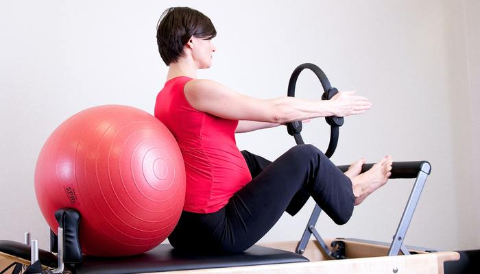 Woman in red top leaning on red stability ball 1103254