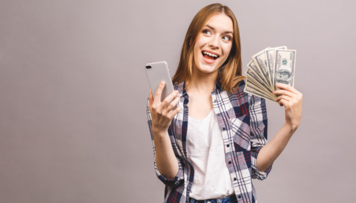 Image excited young lady amazed with mobile phone holding money 255757 838